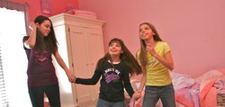 Abby Debrabander, center, dances to a Barney exercise video with her sisters, Amanda Jo, 15, and Kelly, 12. Abby is developmentally disabled. Her parents have applied for Medicaid-funded in-home services designed to help them keep Abby in their home. They've been on the program's waiting list for five years.