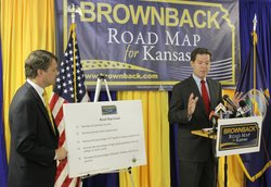 GOP gubernatorial candidate Sam Brownback, right, outlines portions of his &quot;Roadmap for Kansas&quot; plan during a campaign press conference Monday in Topeka. With him is running mate Jeff Colyer, a physician and state senator from Overland Park. Brownback is leaving the U.S. Senate to run for governor.
