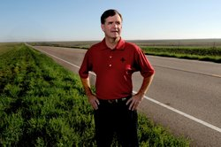 Dr. Bob Moser stands alongside K-27 north of Tribune, the same highway that takes him to Sharon Springs and Syracuse where he practices medicine is medical director of Greeley County Health Services.