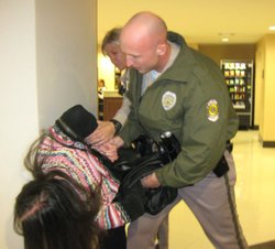 A Wichita police officer tries to restrain a member of Occupy Wichita who protested at a town hall meeting on poverty Wednesday in Wichita.