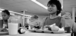 "This boy pictured eating at the LINK charity kitchen in Lawrence is one of eight siblings. His grandmother, who asked that the family not be identified, said she brings several of the children to LINK each Sunday, ""so they can have something to eat on the weekend."" The family receives federal food stamp benefits, the grandmother said, and all members are documented U.S. citizens. Families headed by verified U.S. citizens are not affected by the new SRS policy that has resulted in the children of some undocumented parents being denied food assistance. The policy change has drawn criticism from some who work in community programs that assist the poor."