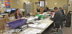 Workers at the state's Medicaid eligibility clearinghouse shown at the sorting tables where mailed and paper application forms are processed and then scanned for entry to the state's computerized enrollment and eligibility system. The front end of the new KEES system is already being used for some sign-ups, foregoing the need for the paper shuffling.
